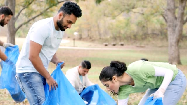 Young man and woman pick up garbage during community outreach event