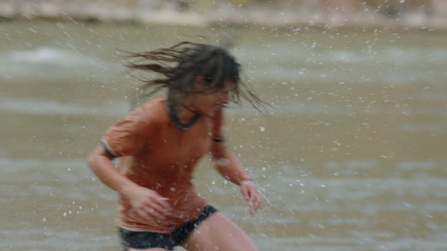 Young man and woman playing in river splash each other with cold water and laugh.