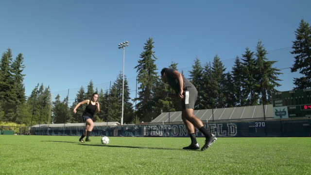 young man and woman playing soccer together - surface level stock videos & royalty-free footage