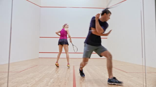 vídeos de stock e filmes b-roll de ld young man and woman playing squash - raqueta