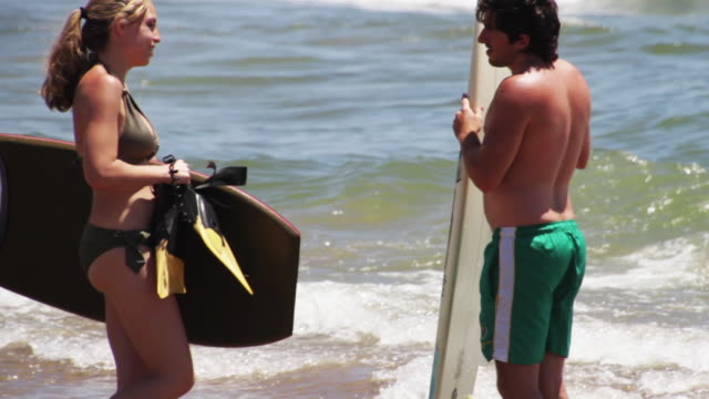 A young man and woman prepare to surf and boogie board
