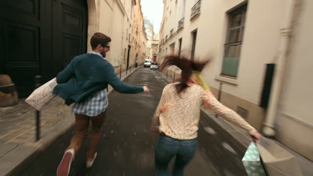 WIDE REAR TRACKING SHOT young couple carrying shopping bags run away from alleyway in Paris