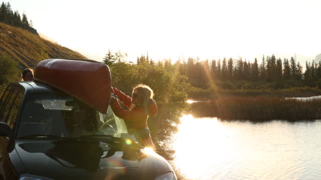 young man and woman remove canoe from car, mountain lake - canoe stock videos & royalty-free footage