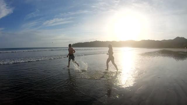 junger mann und frau laufen über strand-gezeiten-wohnungen, stürzen sich ins meer - halbbekleidet stock-videos und b-roll-filmmaterial