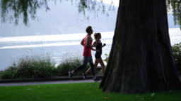 Young man and woman run along lakeside path at sunrise below mountains