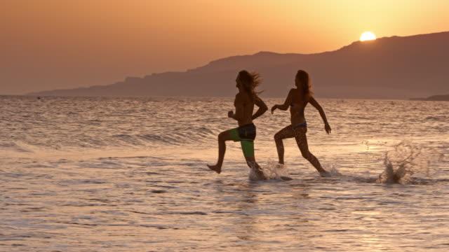 slo mo ung man och kvinna som kör i vattnet vid solnedgången - bar överkropp bildbanksvideor och videomaterial från bakom kulisserna