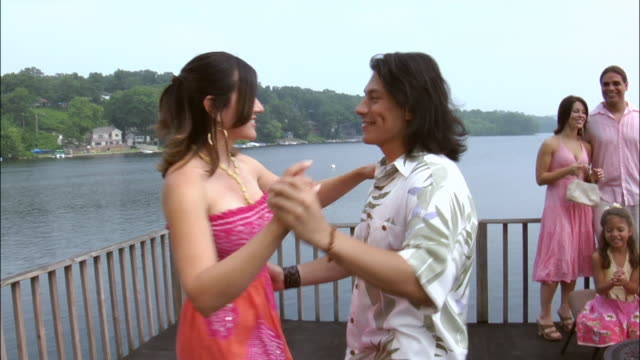 young man and woman salsa dancing on rooftop overlooking lake at party while people watch in background / new jersey - pacific islander background stock videos & royalty-free footage