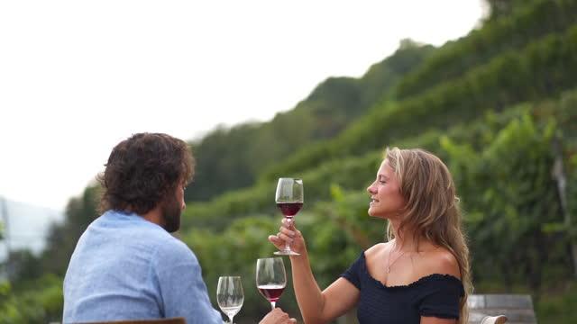 vidéos et rushes de young man and woman sitting down at an outdoor lakeside dinner table - couple hétérosexuel