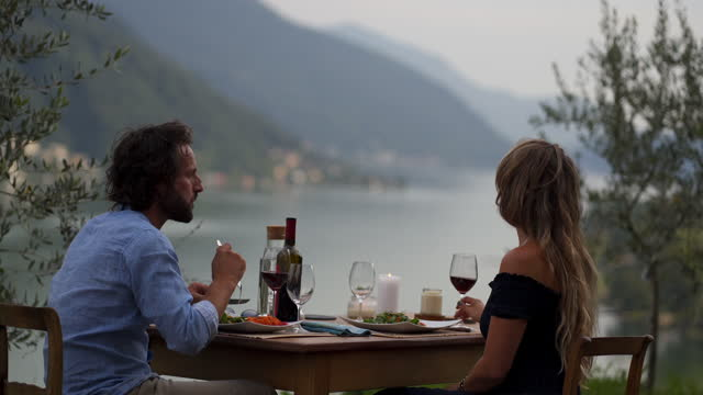 young man and woman sitting down at an outdoor lakeside dinner table - shirt stock videos & royalty-free footage