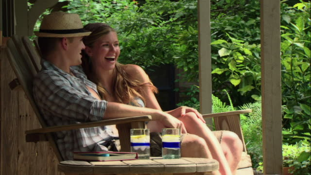 stockvideo's en b-roll-footage met ms young man and woman sitting in rocking chair on porch/ texas - schommelen schommelstoel