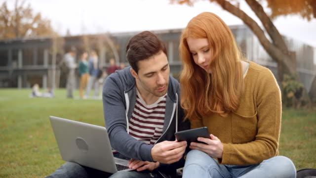 vídeos y material grabado en eventos de stock de hombre joven y mujer sentada en el parque y usando su notebook y tablet - university student