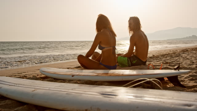 SLO MO Young man and woman sitting on a sandy beach next to their surf boards and talking