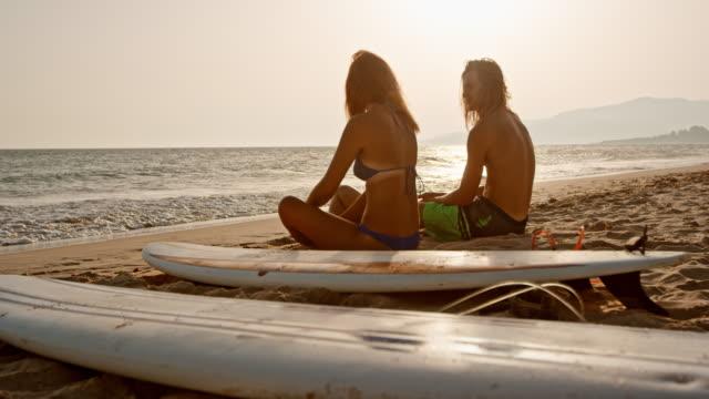SLO MO jeune homme et une femme assise sur une plage de sable à côté de leurs planches de surf et de parler