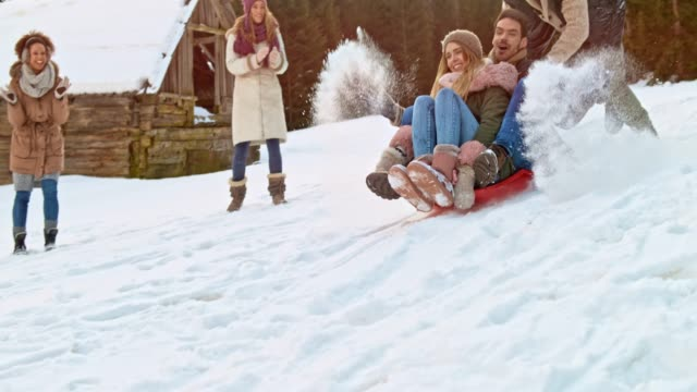 slo mo young man and woman sitting on a sledge being pushed down the hill by a male friend - sliding stock videos & royalty-free footage