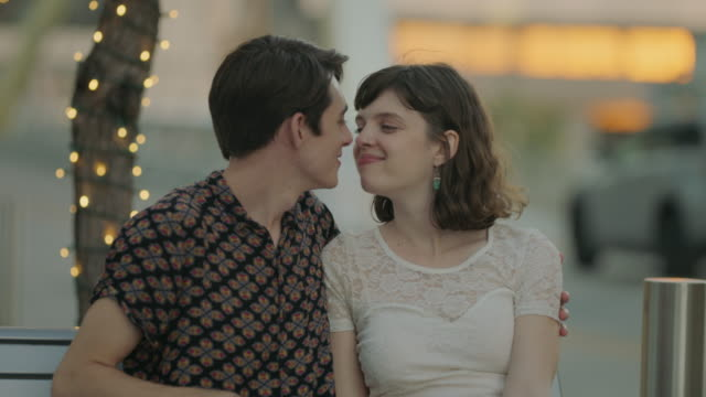 slo mo. young man and woman smile at each other and share a kiss on a romantic night out in downtown austin, texas. - ansikte mot ansikte bildbanksvideor och videomaterial från bakom kulisserna
