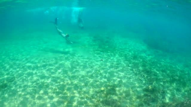 Jonge man en vrouw snorkelen onderwater duiken