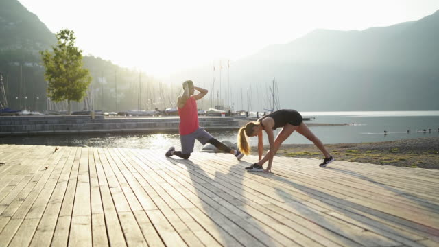 young man and woman stretching along shore of lake below mountains at sunrise - locs hairstyle stock videos & royalty-free footage