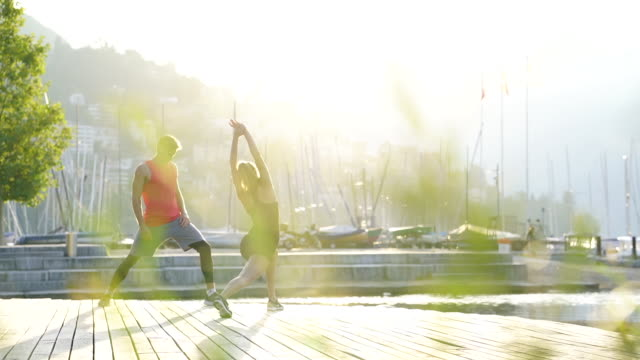 young man and woman stretching along shore of lake below mountains at sunrise - boardwalk stock videos & royalty-free footage
