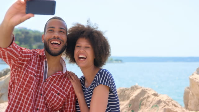 Young man and woman taking a selfie by the sea on a sunny day