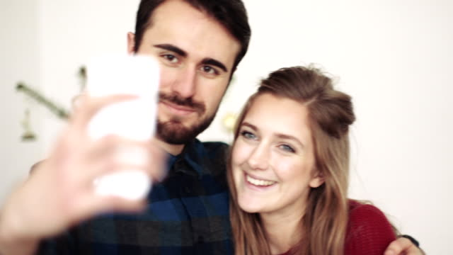 Young man and woman taking selfie with mobile phone during Christmas party