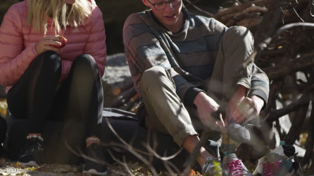 stockvideo's en b-roll-footage met young man and woman talking as he puts on rock climbing shoes - boulder rock