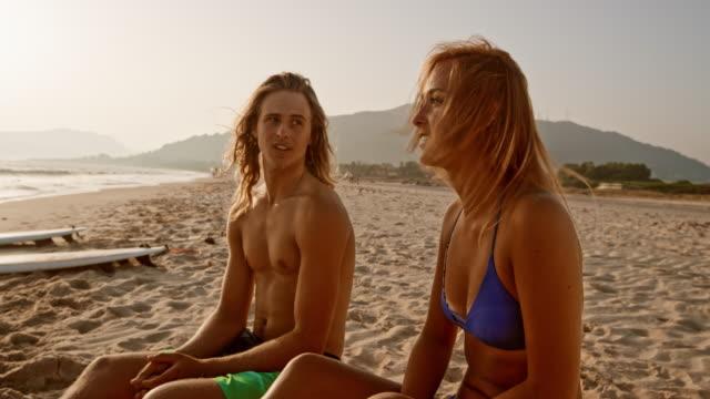 vídeos y material grabado en eventos de stock de hombre joven y mujer hablando en la playa mientras el sol se está poniendo - sin camisa