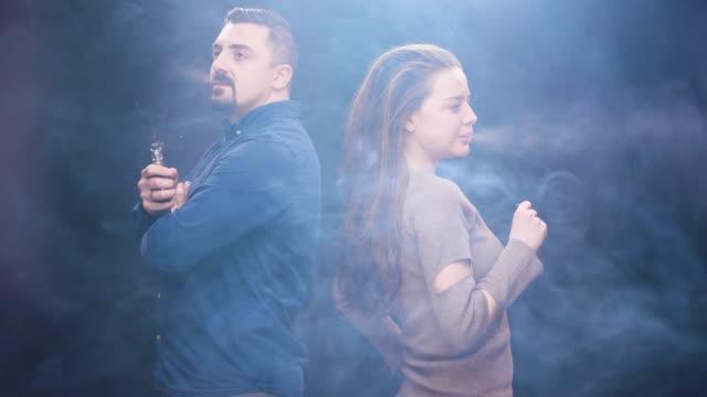 ung man och kvinna vaping röka elektroniska cigaretter långsam tillsammans rörelse - missbrukare av droger bildbanksvideor och videomaterial från bakom kulisserna