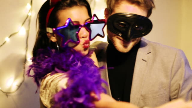 young man and woman wearing funny glasses and masks taking selfie - fancy dress costume stock videos & royalty-free footage