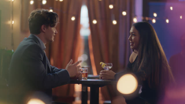 a young man and women have drinks on a first date at a bar - straight hair stock videos & royalty-free footage