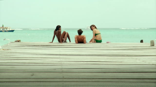 WS Young man and women sitting on jetty by sea / Scarborough, Tobago, Trinidad And Tobago