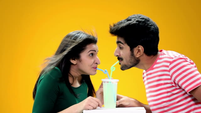 Young man and young woman drinking cold drink