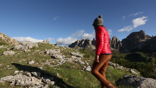 a young man and young woman hiking in the dolomite mountains of italy - down jacket stock videos and b-roll footage