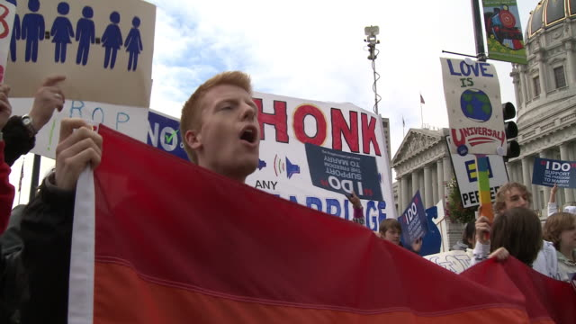 young man and young woman holding rainbow flag and shouting slogan at a samesex marriage rally outside san francisco city hall/ san francisco... - homophobie stock-videos und b-roll-filmmaterial
