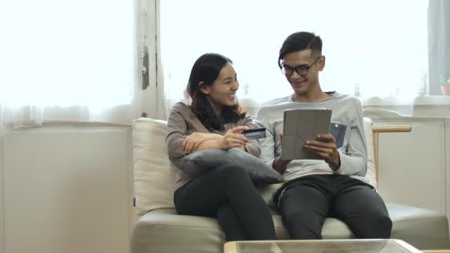 若い男と若い女デジタル タブレットにクレジット カードとオンライン ショッピング - 家の中点の映像素材/bロール
