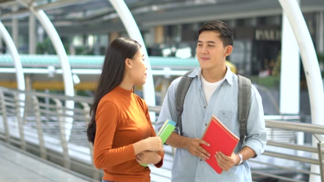 Young man and young woman talking while go to class room