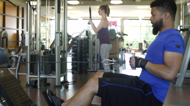 Young man and young woman working out in a gym