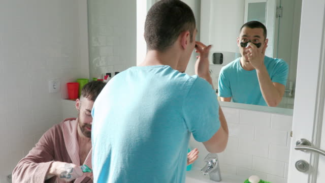young man applying face mask and talking to his boyfriend in the bathroom - skin care stock videos & royalty-free footage