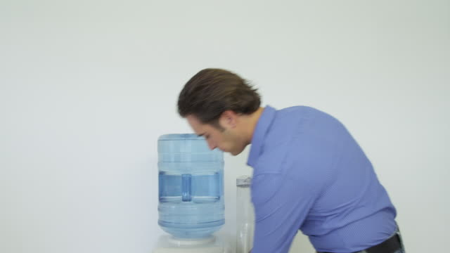 vidéos et rushes de young man approaching water cooler, taking cup and filling it, drinking from cup and exiting frame - fontaine