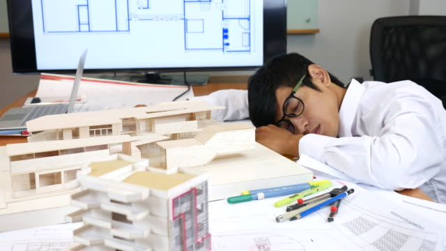 Young man architect sleeping on his Artificial model and blueprints