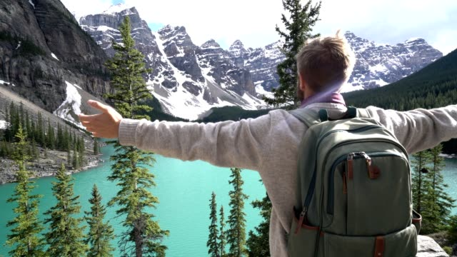 young man arms outstretched at mountain lake - banff stock videos & royalty-free footage