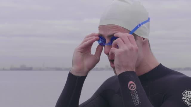 vídeos y material grabado en eventos de stock de young man arranging swimming goggles - gorro de baño