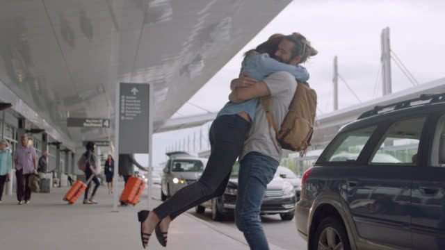 young man arrives and greets hip girlfriend outside airport, spins her around, gets into taxi. - stringere tenere video stock e b–roll