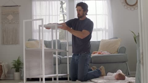 vídeos y material grabado en eventos de stock de young man assembles a flat pack shelf as curious baby watches from blanket on living room floor. - estante muebles