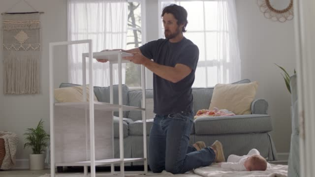 vídeos de stock, filmes e b-roll de young man assembles a flat pack shelf as curious baby watches from blanket on living room floor. - cômodo de casa