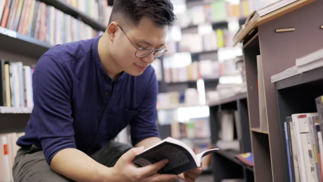 young man at a bookshop choosing a book to buy - korean ethnicity stock videos & royalty-free footage