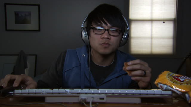 a young man at a keyboard wearing headphones - see other clips from this shoot 1173 stock videos & royalty-free footage