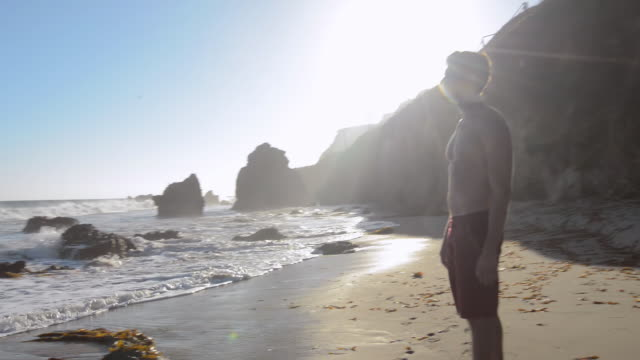 ms zi zo td tu pov young man at beach walking in surf / malibu, california, united states - 男性一人点の映像素材/bロール