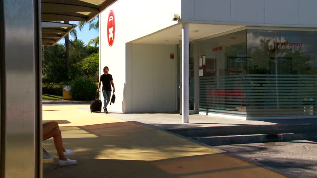 vidéos et rushes de young man at bus station - seulement des jeunes hommes