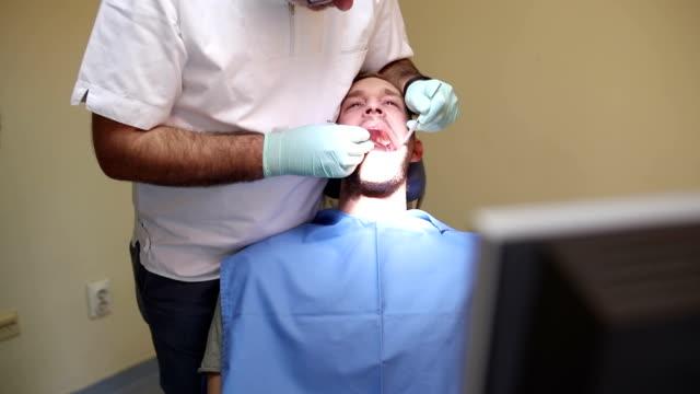 stockvideo's en b-roll-footage met jonge man bij de tandarts, panning shot - tandarts