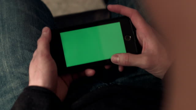 A Young Man at Home Using His Smartphone with Greenscreen